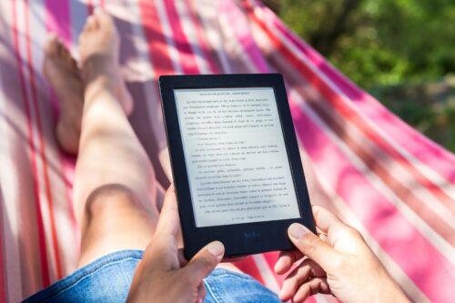 une femme allongée sur un hamac tient un ebook